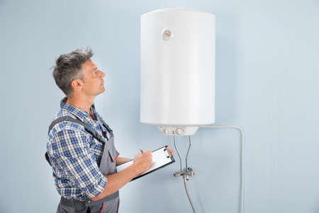 Portrait Of Mid-adult Male Plumber Holding Clipboard Looking At Electric Boiler