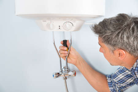 boiler house: Close-up Of Mid-adult Male Plumber Repairing Water Heater