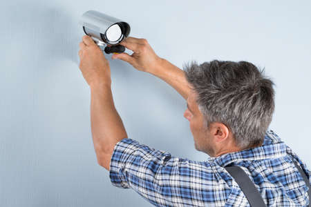 Close-up Of A Technician Adjusting Cctv Camera On Wall