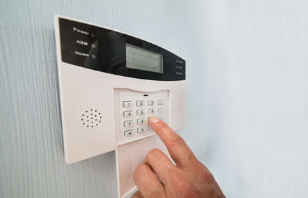 alarm system: Close-up Of A Persons Hand Entering Code In Security System