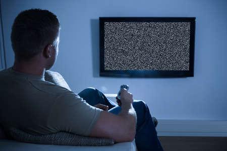 personas viendo television: Hombre sentado en el sof� delante de la televisi�n sin se�al