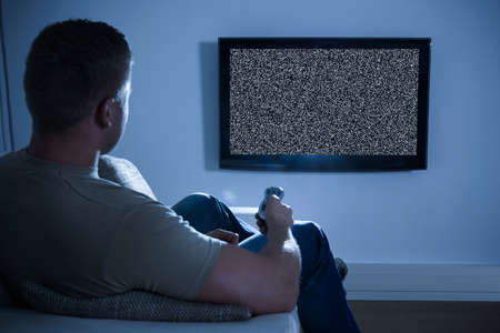 television: Man Sitting On Sofa In Front Of Television With No Signal Stock Photo
