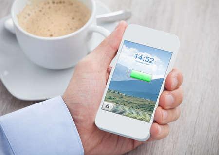 Close-up van de hand houden De mobiele telefoon met opgeladen batterij op een scherm Stockfoto