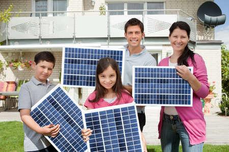 paneles solares: Foto De Familia Feliz Llevar paneles solares Foto de archivo