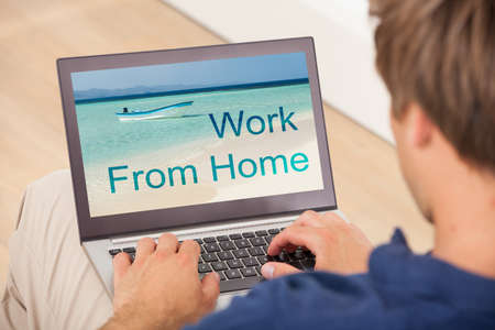 Close-up Of Young Man Working On Laptop At Home photo