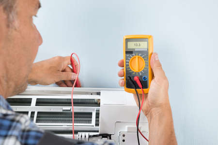 manual test equipment: Portrait Of A Mid-adult Male Technician Testing Air Conditioner With Digital Multimeter