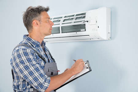 Portrait Of Male Technician Holding Clipboard Looking At Air Conditioner