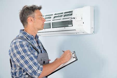 Portret Van Mannelijke Technician Holding Klembord Bij Air Conditioner zoek