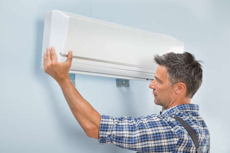 setup man: Portrait Of A Mid-adult Male Technician Fixing Air Conditioner On Wall Stock Photo