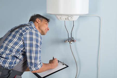 fontanero: Retrato De Hombre fontanero que sostienen el sujetapapeles Mirando a Calentador el�ctrico