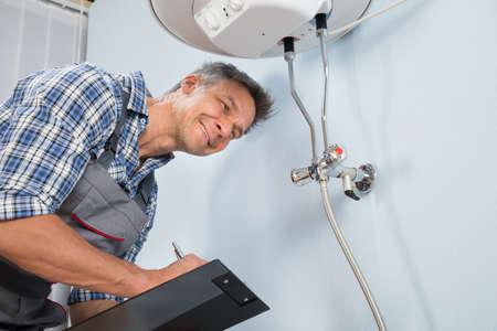 Portret Van Mannelijke Loodgieter Holding Klembord Op Electric Boiler zoek