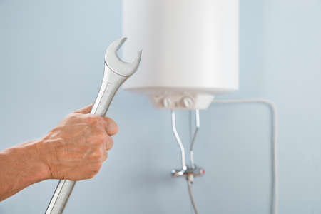 Close-up van een persoon Hand Holding Spanner In De Voorkant Van Elektrische Ketel