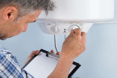 Plumber Holding Clipboard Adjusting Temperature Of Electric Boiler Archivio Fotografico