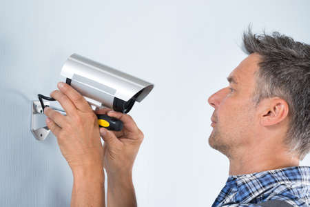 electrician tools: Close-up Of A Technician Adjusting Cctv Camera On Wall