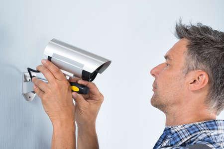 electricista: Primer plano de un técnico Ajuste Cctv En La Pared