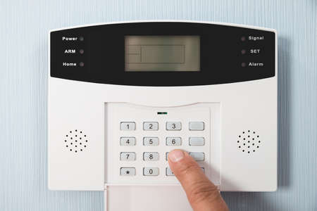 secure home: Close-up Of A Persons Hand Entering Code In Security System