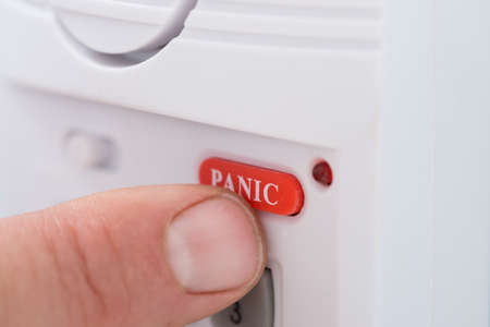 Close-up Of Persons Hand Pressing Panic Button