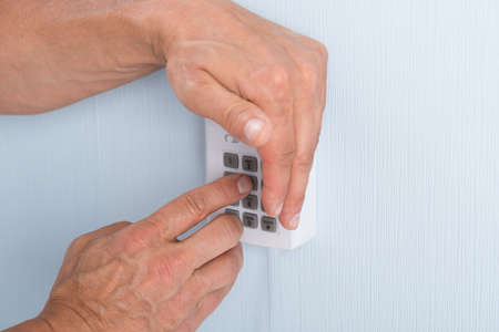 Close-up Of A Hand Entering Pin In Security System photo