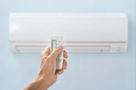 and the air: Close-up Of Persons Hand Holding Remote In Front Of Air Conditioner Stock Photo