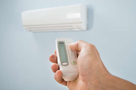 control power: Man Adjusting Temperature Of Air Conditioner Using Remote