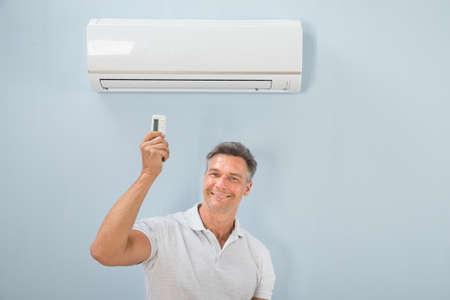 aire puro: Retrato de mediados de adulto Hombre que usa el acondicionador de aire