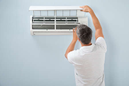 man in air: Rear View Of A Man Cleaning Air Conditioning System