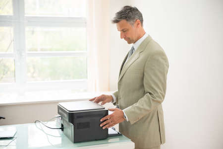 photocopy: Mid-adult Businessman Using Photocopy Machine In Office