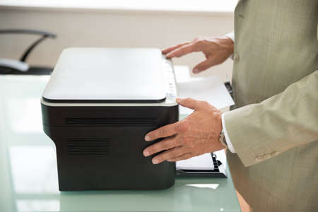 photocopy: Close-up Of A Mid-adult Businessman Using Photocopy Machine In Office