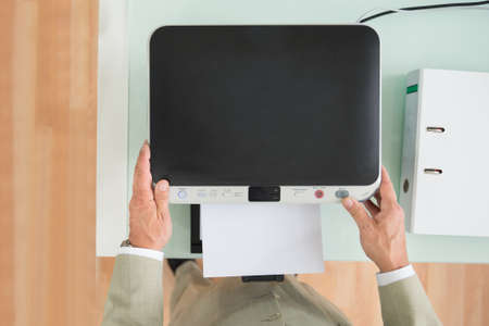 photocopy: High Angle View Of A Businessman Using Photocopy Machine In Office Stock Photo