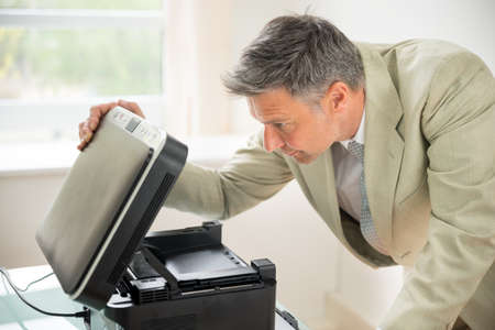 printer cartridge: Close-up Of Mid-adult Businessman In Office Looking At Photocopy Machine