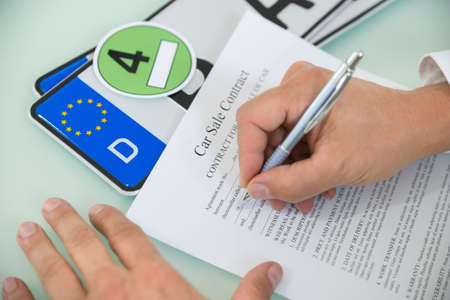 number plate: Close-up Of A Person Filling Car Sale Contract Form With Number Plate On Desk. Contract Paper Contains Placeholder Text