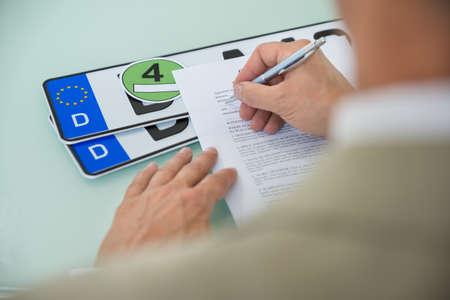 Close-up van een zakenman invullen Car Sale Contract Vorm Met kentekenplaat Op Bureau. Contract Paper bevat plaatsaanduidingstekst