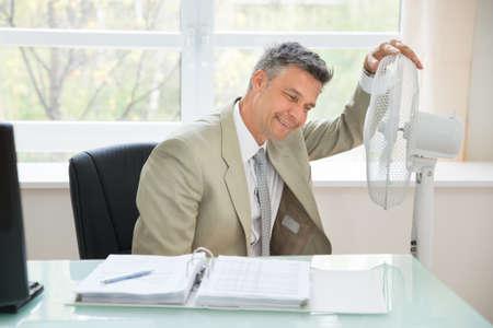 jornada de trabajo: Retrato de un hombre de negocios feliz que se sienta cerca del ventilador En Office