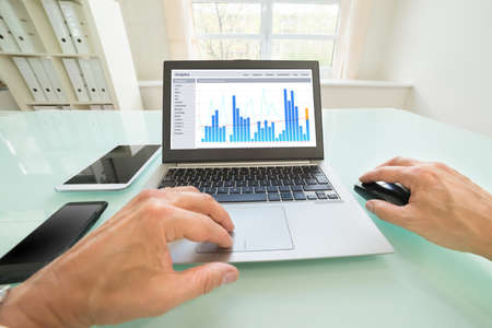 Close-up Of A Person Analyzing Graph On Laptop In Office photo