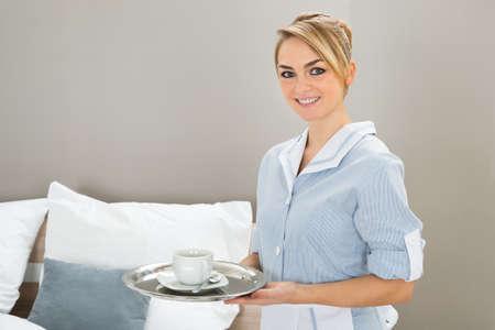 maid: Joven Hermosa Maid Holding Bandeja De Té