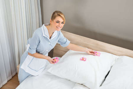 flower bed: Young Maid Decorating Bedroom With Petals Of Hotel Room