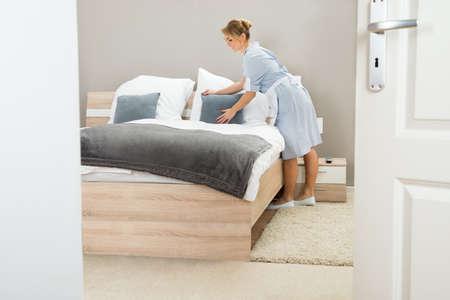 Young Beautiful Pucelle Arranger oreiller sur Bed In Hôtel Room Banque d'images - 39431742