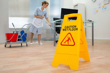 young office: Young Maid Cleaning Floor With Mop In Office Stock Photo