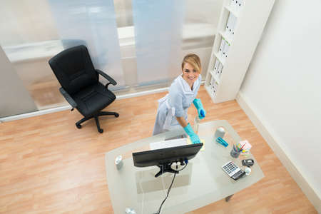 High Angle View Of Young Maid Cleaning Desk In Office photo