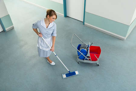 brooming: Happy Female Janitor With Mop And Cleaning Equipment On Floor