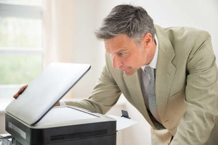 photocopy: Close-up Of Mid-adult Businessman In Office Looking At Photocopy Machine