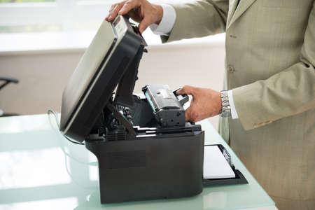 photocopy: Close-up Of Businessman Fixing Cartridge In Photocopy Machine In Office