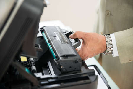 toner: Close-up Of Businessman Fixing Cartridge In Photocopy Machine In Office