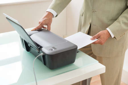 photocopy: Close-up Of A Businessman Using Photocopy Machine In Office Stock Photo