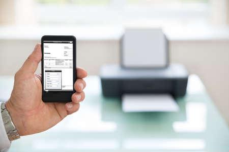 Close-up van een zakenman met Cellphone voor afdrukken Invoice. Fotograaf is eigenaar van het copyright van beelden op het scherm