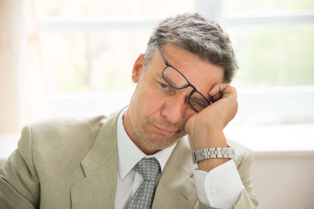 contemplated: Close-up Of Sad Mid-adult Businessman In Office Stock Photo