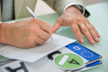 registration: Close-up Of A Businessman Filling Car Sale Contract With Number Plate On Desk. Contract Paper Contains Placeholder Text