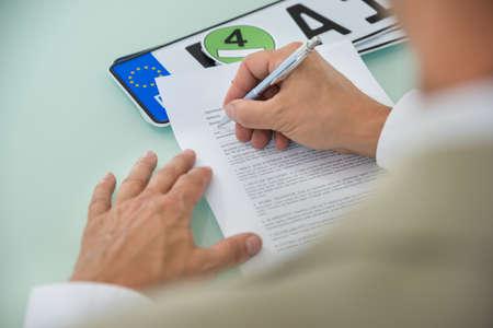 Close-up d'un homme d'affaires de remplissage Vente de voitures formulaire de contrat avec plaque d'immatriculation sur le bureau. Papier contrat contient le texte de substitution
