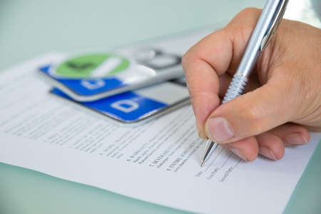 placeholder: Close-up Of A Hand Filling Car Sale Contract Form With Vehicle Registration Plate On Desk. Contract Paper Contains Placeholder Text