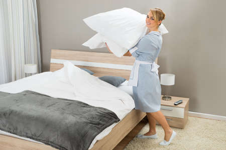 hotel worker: Happy Female Housekeeping Worker With Pillows In Hotel Room